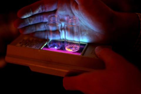 Die organischen Substanzen leuchten, wenn sie durch UV-Strahlung angeregt werden. (Foto: Marcin Szczepanski, UMich)
