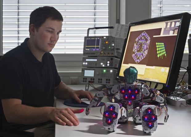Philipp Mittendorfer mit dem Roboter Bioloid, auf dessen Körper 31 sechseckige Sensormodule angebracht sind (Foto: Andreas Heddergott / TU München)