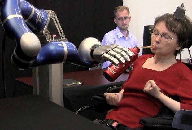 Cathy trinkt aus der Flasche, die ihr der DLR-Roboterarm anreicht. Sie steuert ihn... (Bild: Brown University)