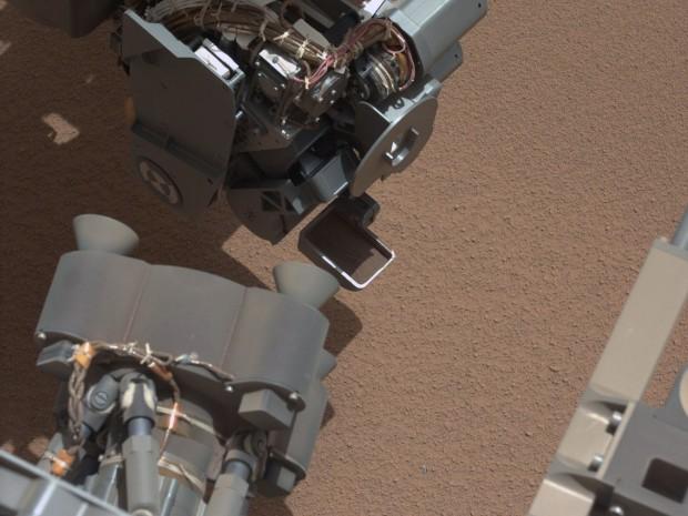 Curiositys gefüllte Probenschaufel. Im Vordergrund liegt ein winziges glänzendes Teilchen auf dem Boden, das die Nasa-Forscher in Aufregung versetzt hat. (Foto: Nasa/JPL-Caltech/MSSS)