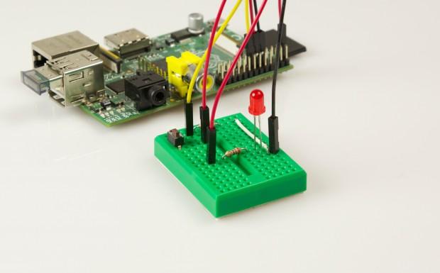 Unser einfaches Projekt: Eine LED und ein Taster auf einem Breadboard. Im Raspberry Pi steckt ein Bluetooth-Dongle für USB. (Golem.de)