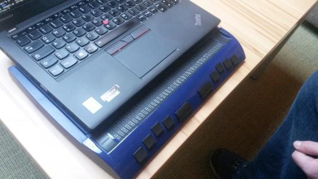 Eine elektronische Braille-Zeile ist an Schöppleins Laptop angeschlossen. Sie nutzt er zum Lesen, zum Schreiben wechselt er auf die normale Tastatur. (Bild: Julia Ley)