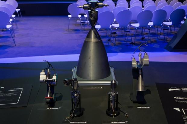 """Einfache Satellitentriebwerke. Ein oder zwei Ventile, Brennkammer, Düse. Darunter steht als Überschrift """"Satellitentriebwerke - Zukunftstechnologien - Chemischer Antrieb"""" (Foto: Werner Pluta/Golem.de)"""