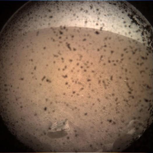 Das erste Bild von Mars Insight nach der Landung auf dem Mars. Die durchsichtige Schutzkappe wird später von der Kamera entfernt.