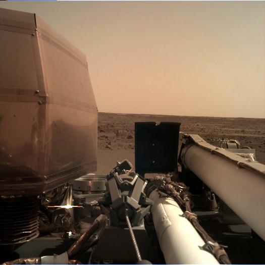 Ein Bild der Instrument Deployment Camera zeigt einen intakten Lander, nachdem die Solarzellen ausgeklappt wurden. Unter der Verkleidung auf der linken Seite befindet sich das Seismometer.