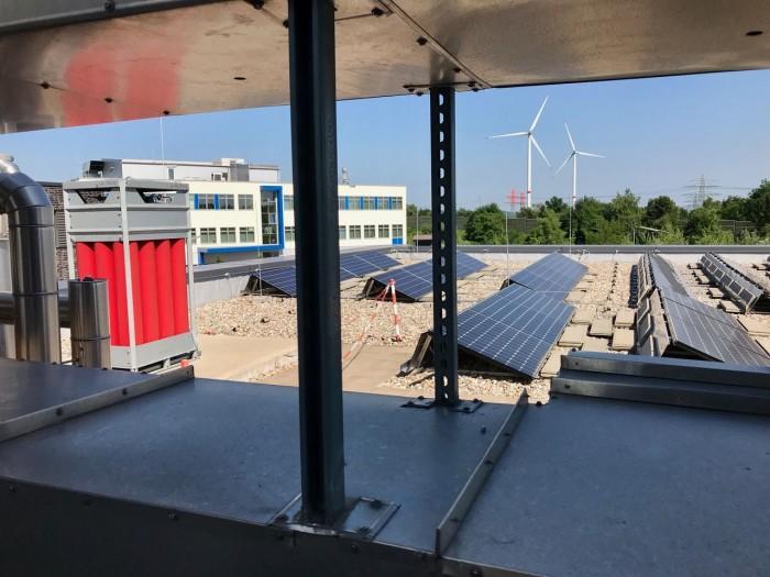 Auf dem Dach des Technologiezentrums: die Photovoltaik-Anlage, der Wasserstoffspeicher (rot) und der hochschuleigene Windpark (Bild: Monika Rößiger)