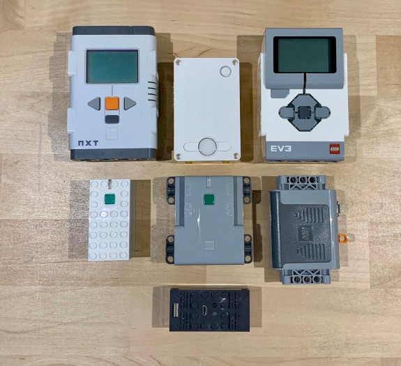 Treffen der Generationen und ein Fremder: die mehr oder weniger smarten Batterieboxen beziehungsweise Hubs von Lego. Von links oben nach rechts unten: Mindstorms NXT, Spike Prime, Mindstorms EV3, Powered Up, Control+, Power Functions, Buwizz (nicht Lego) (Bild: Jan Rähm)
