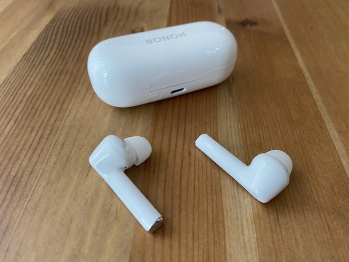 Das geschlossene Ladeetui mit sichtbarer USB-C-Buchse mit den davor liegenden Magic Earbuds (Bild: Ingo Pakalski/Golem.de)