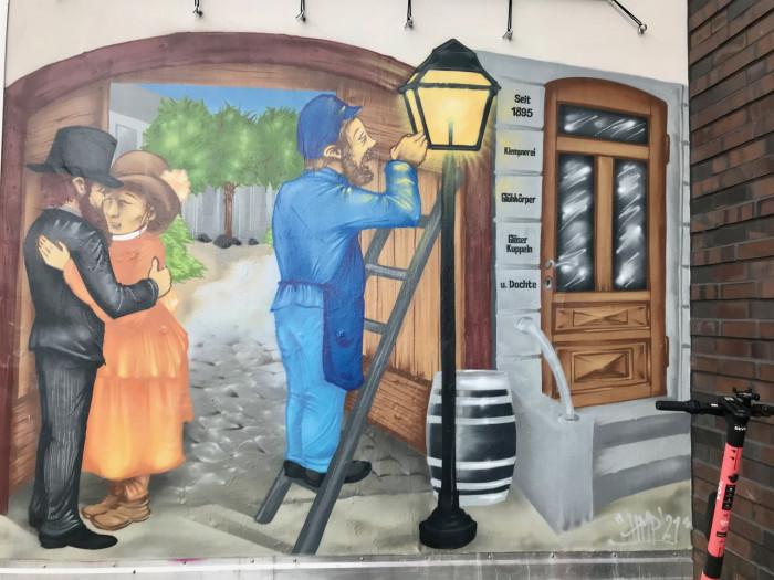 Ein Wandbild zeigt, wie es früher war: Gelb-orange flackernde Gaslaternen warfen ihr schummriges Licht auf die Straßen und Wege.(Bild: Monika Rößiger)
